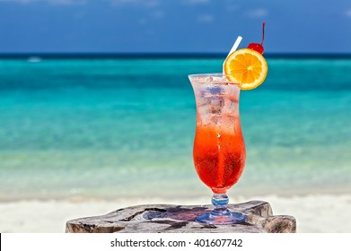 Glass of red drink is on the beach table, Maldives, The Indian Ocean