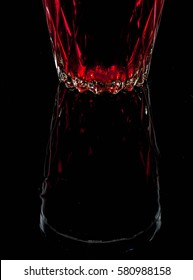 A glass with red drink on a dark background. Space for text.