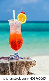 Glass of red drink is on the original beach table, Maldives, The Indian Ocean