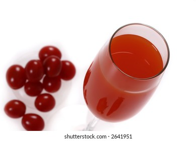 a glass of red drink with out-of-focused cherry tomatoes
