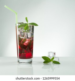 Glass of Red juice and ice cubes with mint on white background