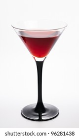 Glass with red martini on white background