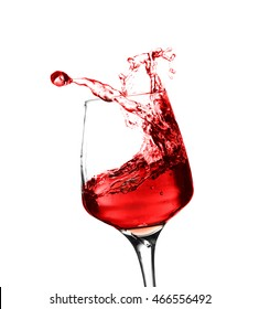 Glass of red splashing wine isolated on white