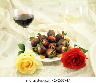 A glass of red and white wine with chocolate covered strawberries, chocolate covered apricots and roses.