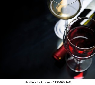 Glass of red and white wine on black background. Wine list design menu with copyspace. Alcohol beverage card backdrop.