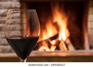 Glass of red wine against cozy fireplace background, in country house, horizontal, hygge , home sweet home.