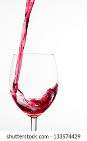 a glass of red wine is being poured