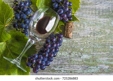 glass of red wine and black grapes with leaves on rustic background,selective focus/wine concept