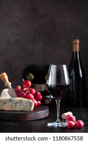 Glass of red wine with blue cheese and grapes on background bottle of wine