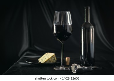 A glass of red wine with blue cheese. Bottle of red wine on a black background