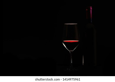 A glass of red wine and a wine bottle against a black background