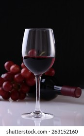 Glass of red wine, bottle and red grape on black background