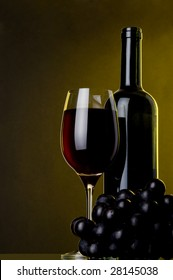 a glass of red wine bottle and grape