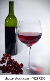 Glass of red wine, bottle and grapes