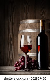 Glass of red wine with bottle and keg standing on a wooden background