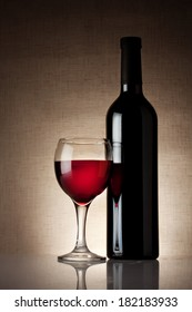 Glass of red wine with a bottle on burlap background