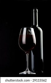 a glass of red wine and a bottle on  black background