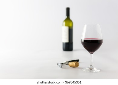 Glass of red wine and bottle on a white background with cork and corkscrew