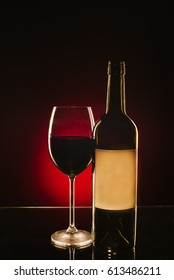 A glass of red wine and a bottle on a glass table.