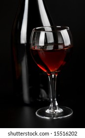 glass of red wine and bottle over black background