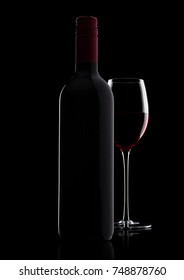 Glass of red wine with bottle with shape on black background with reflection