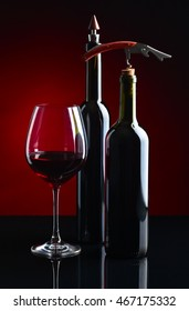 Glass of red wine and bottles on black background
