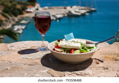 A glass of red wine and bowl of greek salad with greek flag on by the sea view, summer greek holidays concept.