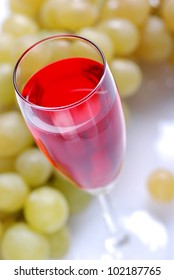 glass of red wine with bunches of grapes