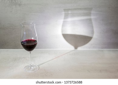 Glass of red wine casts shadow on gray background