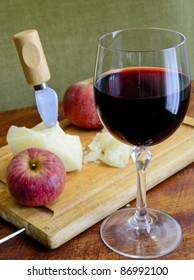 glass of red wine with cheese and apple on a chopping board