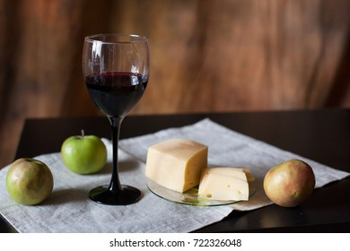A glass of red wine, cheese and apples on a dark background