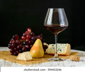 Glass of red wine with cheese, pear and grapes on a white table and black background