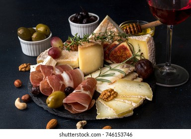 Glass of red wine and cheese plate with pieces moldy cheese, prosciutto, pickled plums, olives, grapes, figs, honey, pear, nuts on black slate background.