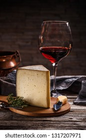 Glass of red wine and cheese still life on wooden background