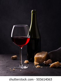 Glass of red wine, cheeses and cheese knife on black background