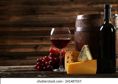 Glass of red wine, cheeses and grapes on brown wooden background