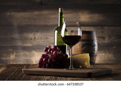 Glass of red wine, cheeses and grapes on old wooden table. Old wooden background.