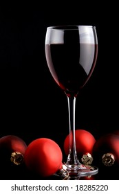 a glass of red wine and Christmas decorations