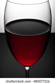 Glass of red wine close up photography on black board and white background