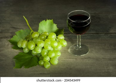 glass of red wine with a cluster of grapes on old wooden table