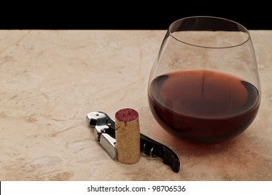 Glass of red wine with cork screw and fresh cork
