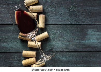 A glass of red wine and wine corks on a dark background. A retro-styled wine tasting invitation, horizontal design template with copy space