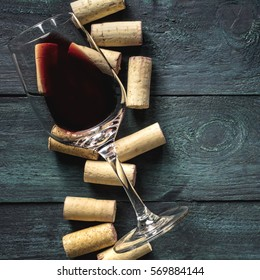 A glass of red wine and wine corks on a dark background. A retro-styled wine tasting invitation, square design template with copy space
