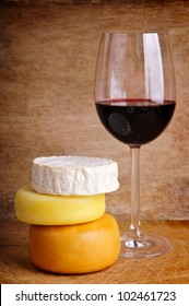 glass of red wine with different cheese on a vintage wooden background