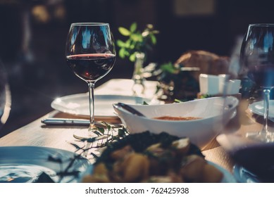 Glass of red wine at dining table in backyard patio