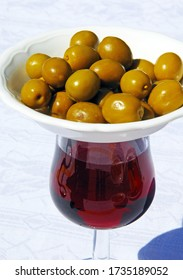 Glass of red wine with dish of green olives on top to keep flies off (modern tapas originates from the the word tapa meaning to cover), Costa del Sol, Malaga Province, Andalucia, Spain, Europe.