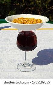 Glass of red wine with dish of peanuts on top to keep flies off (modern tapas originates from the the word tapa meaning to cover), Costa del Sol, Malaga Province, Andalucia, Spain, Europe.