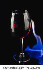 A glass of red wine in the fire, a tall wine glass, wine on a black background