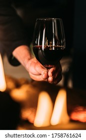 A glass of red wine with a fireplace. Hand holding glass.