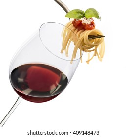 glass with red wine and fork with spaghetti